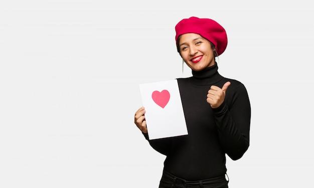笑顔で親指を上げるバレンタインデーの若い女性