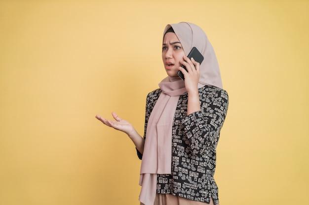Молодой женщине в чадре звонят по мобильному телефону, и она злится