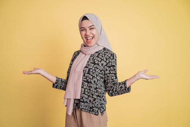 베일을 쓴 젊은 여성이 매우 행복한 몸짓으로 활짝 웃고 있다
