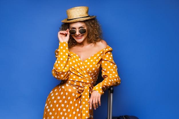 Молодая женщина в винтажном платье остается на чемодане
