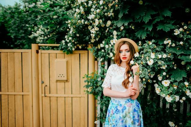 Молодая женщина в винтажной длинной юбке, старомодном топе с вьющимися рыжими волосами и соломенной шляпе, стоящей в кустах с деревянным забором