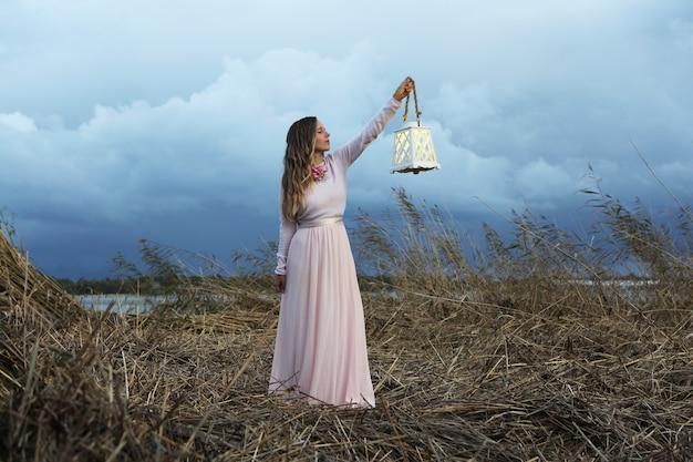 바다 근처 회색 잔디에 랜턴과 함께 서 있는 빈티지 핑크 긴 드레스에 젊은 여자