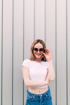 Молодая женщина в винтажных очках в стильной брендовой одежде возле металлической полосатой стены