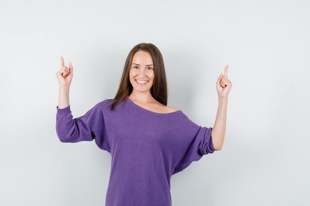 紫色のシャツを着た若い女性が指を上に向けて幸せそうに見える、正面図。