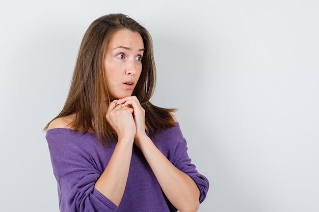 Молодая женщина в фиолетовой рубашке подпирает подбородок сложенными руками и выглядит удивленным, вид спереди.