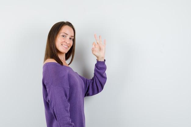 大丈夫なジェスチャーを示し、楽観的に見える紫色のシャツの若い女性。