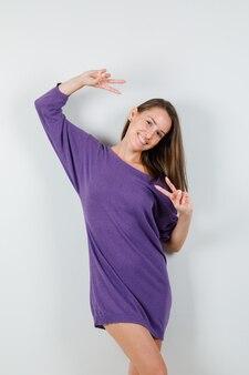 Молодая женщина в фиолетовой рубашке показывает v-знак и выглядит счастливым, вид спереди.