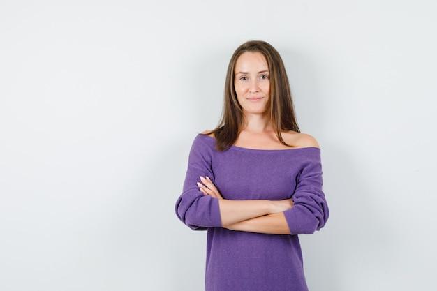 Молодая женщина в фиолетовой рубашке, стоя со скрещенными руками и улыбаясь, вид спереди.
