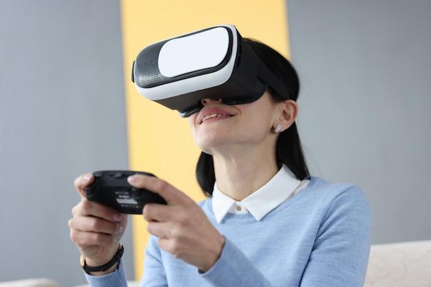 ジョイスティックを保持している仮想現実メガネの若い女性。ギャンブル依存症の概念
