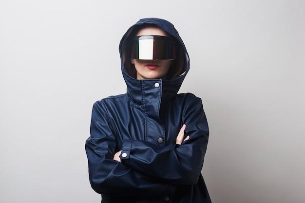 Молодая женщина в очках виртуальной реальности, в синей куртке со скрещенными руками на светлом фоне.