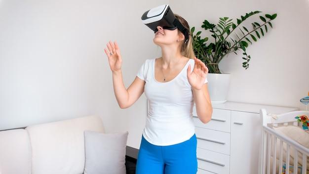 Молодая женщина в очках или гарнитуре виртуальной реальности смотрит панорамное видео на 360 градусов дома.