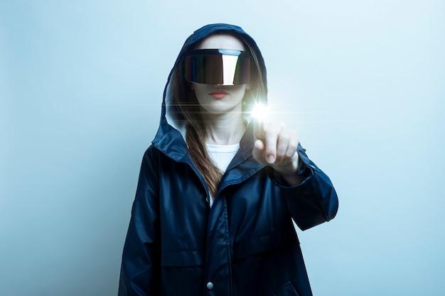 가상 현실 안경을 쓴 젊은 여성이 터치스크린에서 손가락을 누르고 밝은 배경에 그라디언트를 추가합니다.