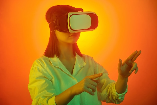 Молодая женщина в гарнитуре vr, указывая на виртуальный дисплей во время подготовки презентации