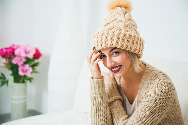 집에서 따뜻한 베이지 색 손 니트 모자에 젊은 여자