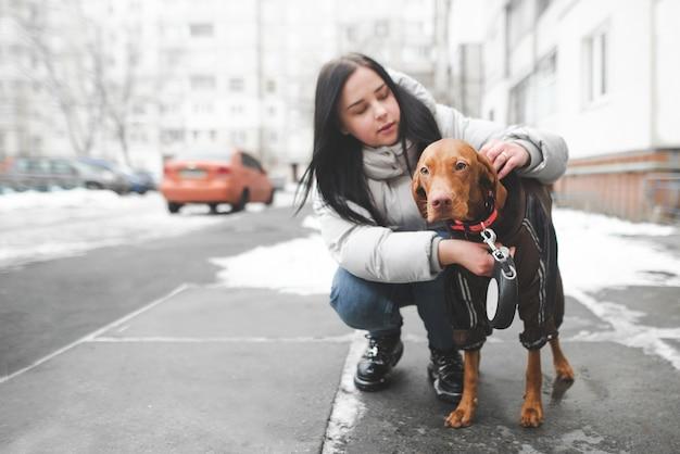 暖かい服を着た若い女性が犬と一緒に地面に座っているし、襟を調整します