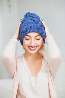 집에서 따뜻한 진한 파란색 손 니트 모자에 젊은 여자