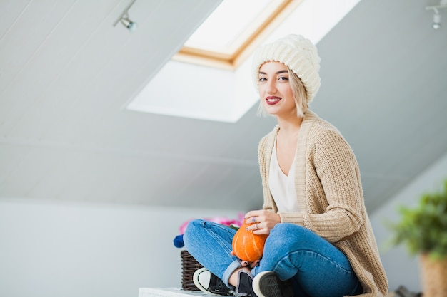 집에서 따뜻한 손 니트 모자에 젊은 여자