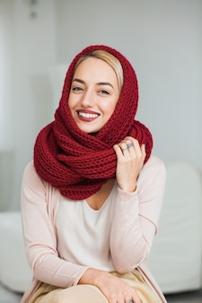 집에서 따뜻한 손 니트 목줄 스카프에 젊은 여자