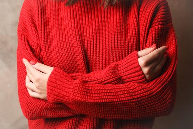 暖かい赤いセーター、クローズアップの若い女性。テキストのためのスペース