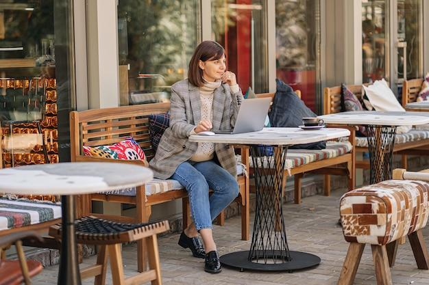 Молодая женщина в теплом свитере и блейзере работает над нетбуком в кафе на террасе. осеннее утро. уличный стиль.