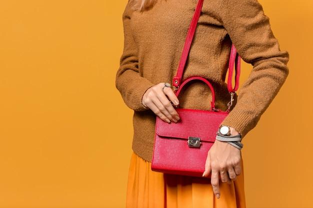 Молодая женщина в теплом свитере и стильной сумке на цветной поверхности