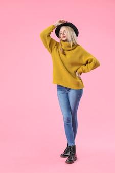 Молодая женщина в теплом свитере на цветной поверхности