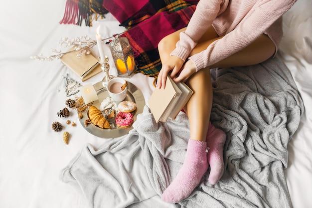 暖かいウールの服の若い女性は明るい日当たりの良い家で彼女のベッドに座っています。