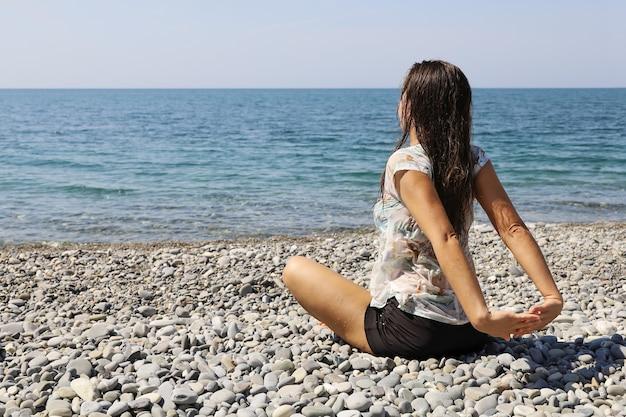 Молодая женщина в мокрой одежде сидит на галечном пляже и протягивает руки за спиной