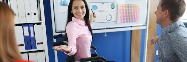 휠체어에 젊은 여자는 사무실에서 칠판에 사업 사람들의 그룹을 가르치고