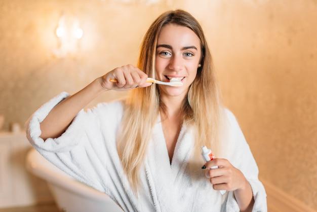 歯ブラシ、バスルームのインテリアで彼女の歯を磨く白いバスローブの若い女性