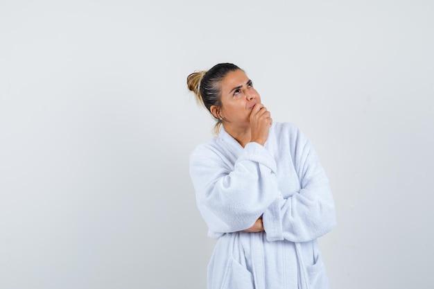 思考ポーズで立って物思いにふける白いバスローブを着た若い女性