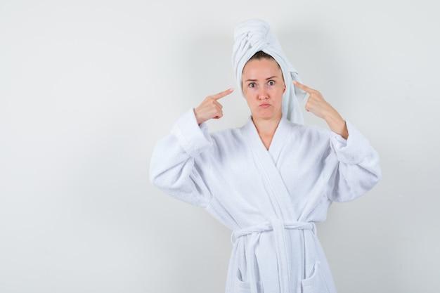 白いバスローブを着た若い女性、彼女の頭を指して困惑しているように見えるタオル、正面図。