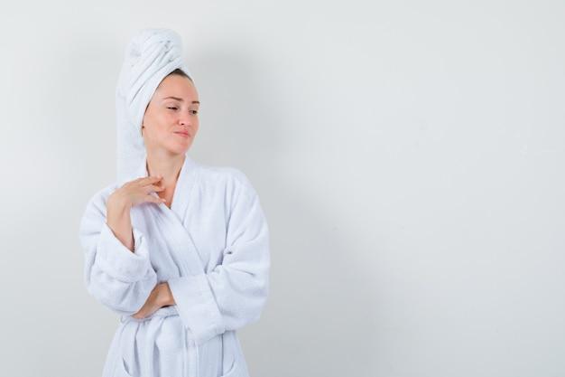 Молодая женщина в белом халате, полотенце позирует, глядя в сторону и очаровательно, вид спереди.