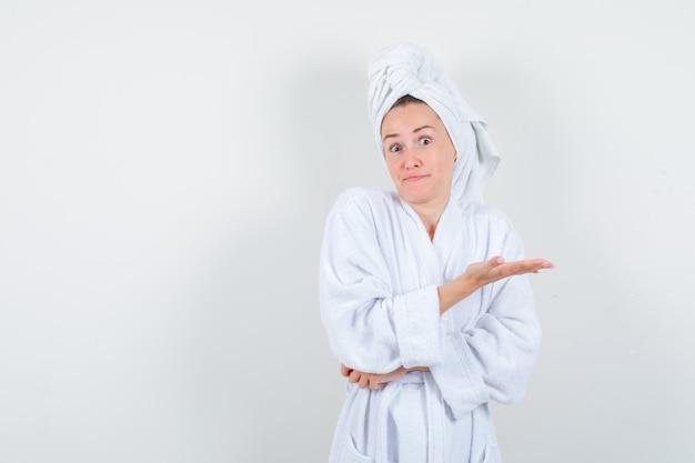 白いバスローブを着た若い女性、何かを見せるために手のひらを広げて困惑しているように見えるタオル、正面図。
