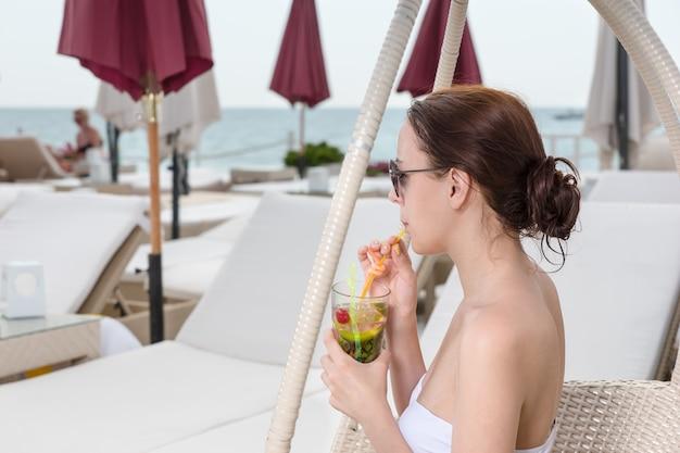 ラグジュアリーバケーションリゾートのオーシャンフロントデッキの籐の椅子に座っている間わらを通して熱帯の飲み物をすすりながら白いビキニの若い女性
