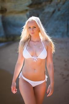 Молодая женщина в белом бикини гуляет по пляжу