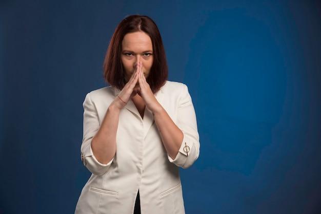 흰색 재킷에 젊은 여자는 똑똑해 보인다.