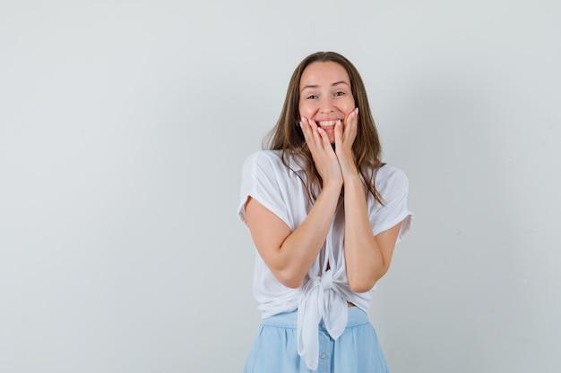 Молодая женщина в белой блузке и голубой юбке держится за щеки и выглядит счастливой