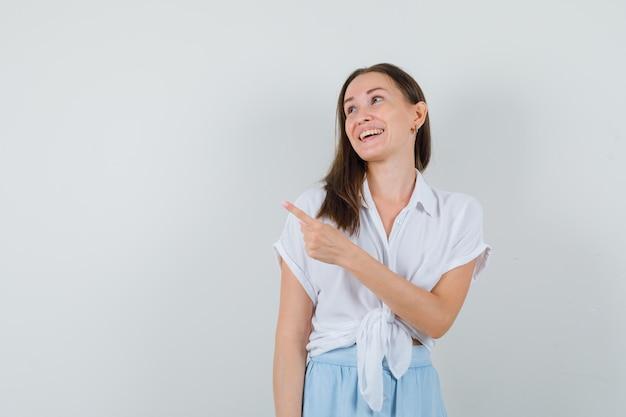 白いブラウスと水色のスカートの若い女性は、人差し指で左を指して、陽気に見えます