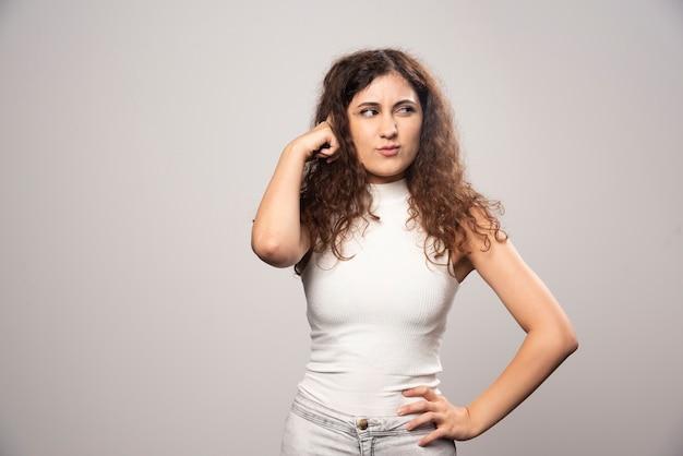 白い壁の上に立っている白いブラウスの若い女性。高品質の写真