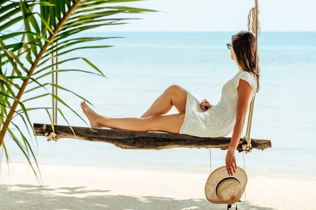 白いドレスと帽子の若い女性がビーチで揺れる
