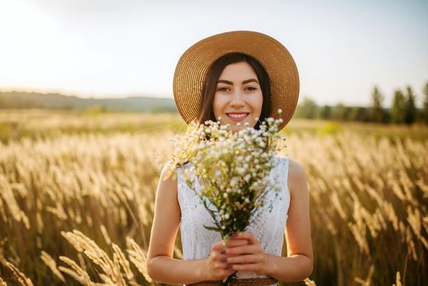 Молодая женщина в белом платье и соломенной шляпе с букетом полевых цветов на ржаном поле. милая девушка на летнем лугу