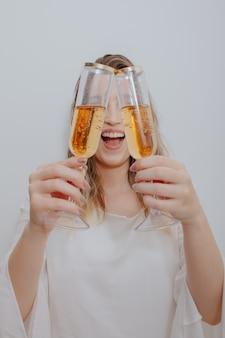 흰 드레스와 그녀의 얼굴 앞에서 손에 스파클링 와인 두 잔을 가진 젊은 여자