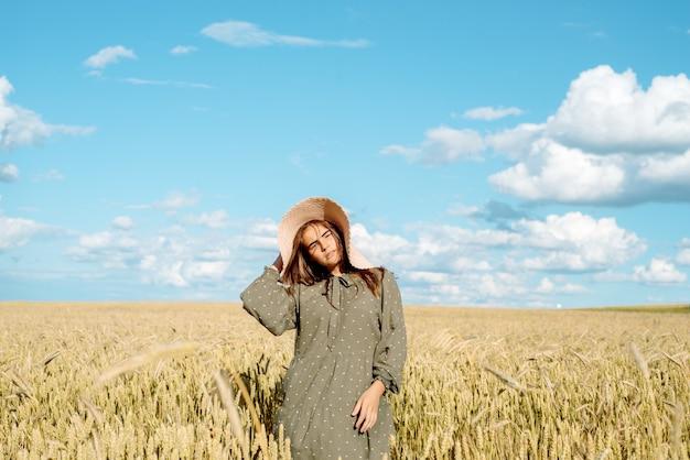 白いドレス、麦わら帽子、花畑、パンの穂の若い女性。花畑を楽しんで、屋外でリラックス、調和の自由の概念の美しい少女。