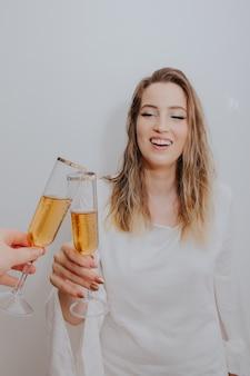 手にスパークリングワインのガラスで乾杯白いドレスの若い女性