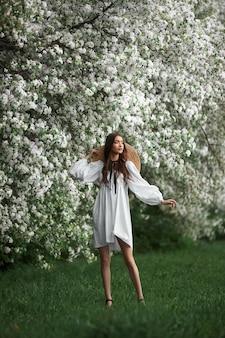 밀짚모자를 쓴 하얀 드레스를 입은 젊은 여성이 꽃이 만발한 봄 정원 공원을 산책합니다. 봄이 왔다 로맨틱 무드
