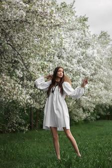 麦わら帽子をかぶった白いドレスを着た若い女性が咲く春のガーデンパークを歩きます。春が来た、ロマンチックな気分