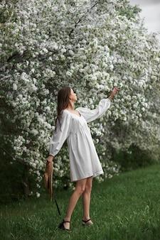 Молодая женщина в белом платье с соломенной шляпой гуляет по цветущему весеннему саду. пришла весна, романтическое настроение
