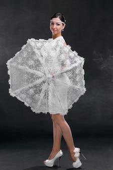 회색 배경에 흰색 우산을 쓴 흰색 드레스를 입은 젊은 여성