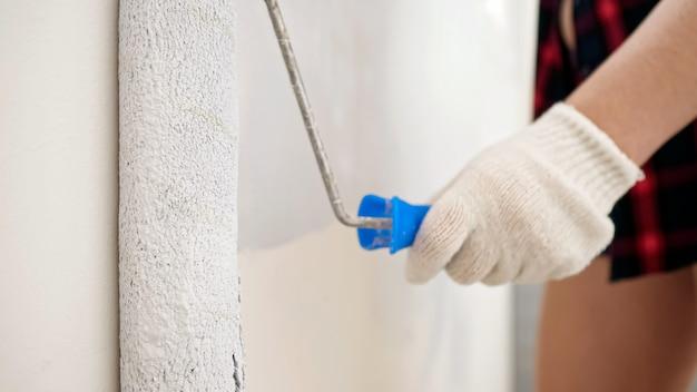 白い手袋をはめた若い女性は、広々とした明るく照らされた部屋の極端なクローズビューで修理を行うローラーで明るい灰色の壁をペイントします